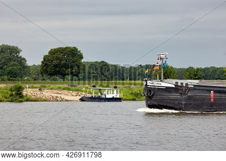 Arcen, The Netherlands - June 24, 2021: Small Ferry Crossing Dutch River Meuse Waiting For Large Car