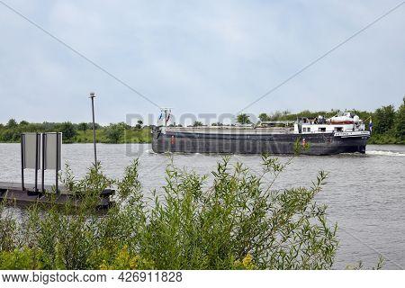 Arcen, The Netherlands - June 24, 2021: Cargo Ship Sailing At Dutch River Meuse Near Village Arcen