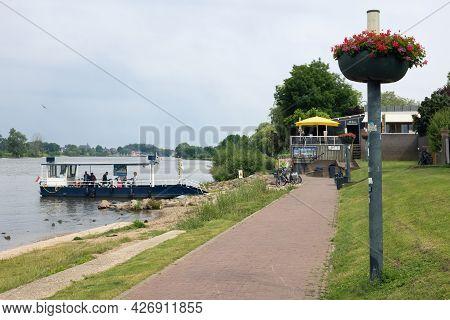 Arcen, The Netherlands - June 24, 2021: Small Ferry Crossing River Meuse Near Dutch Village Arcen