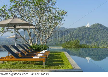 Save\ndownload Preview\nchaise Longues Near A Swimming Pool With Blue Sky And Mountain In The Backgr