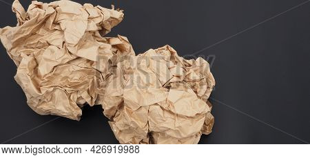 Crumpled Brown Paper.it Is Mauled On Black Background.