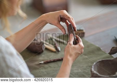 Potter Female Kneads A Piece Of Clay With Her Hands In Her Studio Workshop. Pottery Made Of Clay Wit