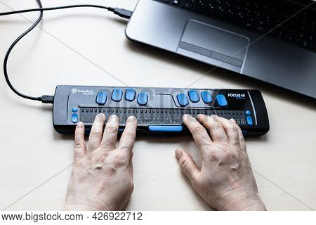 Moscow, Russia - June 5, 2021: Reading With Focus 40 Blue Braille Display. Freedom Scientific Is The