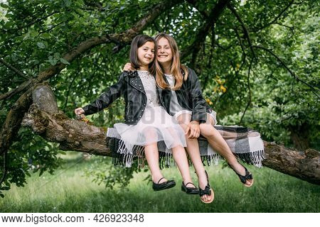 Beautiful Little Ladies Hugging Each Other While Sitting Together On Tree Branch. Two Pretty Sisters
