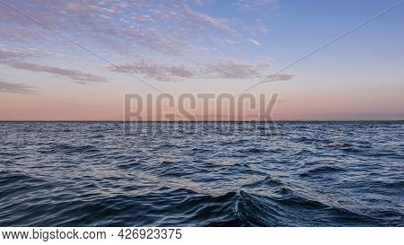 Gentle Sunset Over The Atlantic Ocean. Azure Sky Highlighted Pink Over The Horizon. Light Lilac Clou