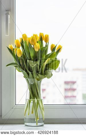 Fresh Yellow Tulip Flowers In Glass Vase On Window Sill At Home With Cityscape On Background