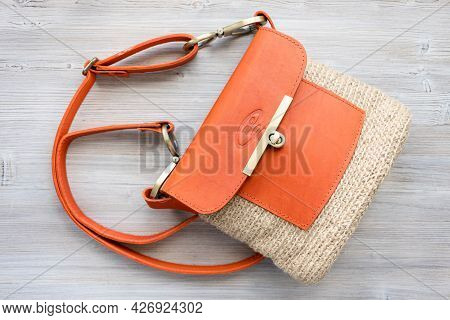 Top View Of Hand-knitted Casual Cross Body Bag With Orange Leather Cover On Gray Wooden Table