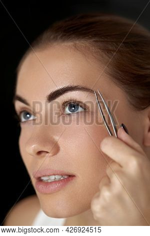 Eyebrow Correction.  Plucking Eyebrows. Beautiful Young Woman With Tweezers. Model With Beauty Face.