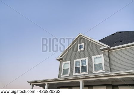 Low Angle View Of A Traditional Home With Gray Vinyl Wall Siding