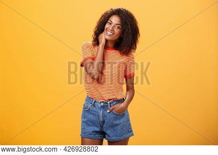 Stylish African American Slim Woman With Curly Medium Hair Holding Hand In Denim Shorts Tilting Head