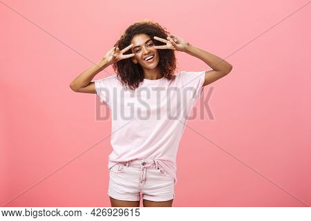 Indoor Shot Of Charismatic Playful Dark-skinned Woman With Afro Hairstyle Tilting Head Showing Peace