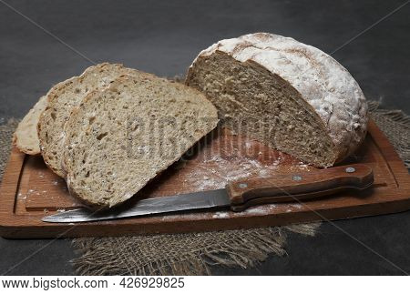 Homemade Bread From Coarse Flour With Spices, With Flax And Sunflower Seeds Cut On A Wood Board. Sou