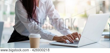 Close Up Of Tanned Woman's Hands On A Computer Keyboard. She Is Typing. There Is A Piece Of Paper Wi