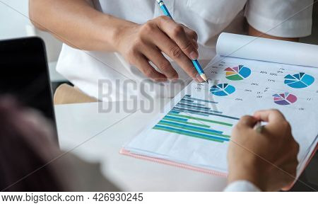 Business Team Analyzing Income Charts And Graphs With Modern Laptop Computer. Top View Close Up Busi