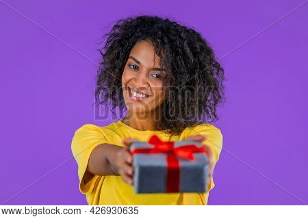 Mixed Race Woman With Curly Hair Gives Gift Box By Hands To Camera On Purple Studio Background. Girl