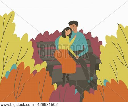 A Loving Couple Sits On A Bench In An Autumn Park In An Embrace. Multicolored Autumn Season. The Con