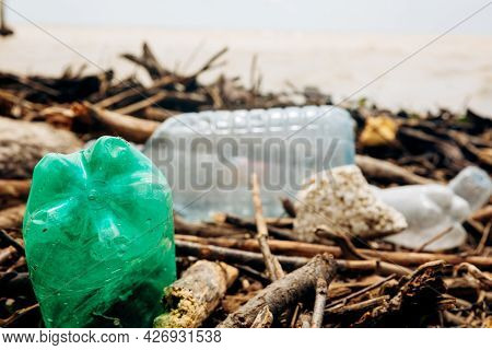 The Sea Coast After The Storm. Plastic And Wood Waste On The Beach Pollute The Environment. An Envir
