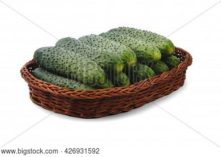 Cucumbers In A Dark Flat Basket Isolated On White.