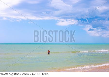 Beautiful Azure Sea And Blue Sky On The Horizon. A Man In The Water In The Background. Idyllic Sea L