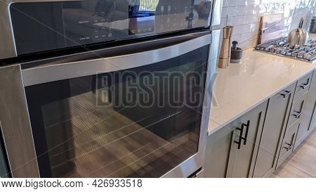 Pano Oven And Countertop With Stove Inside The Kitchen Of Home With Wooden Floor
