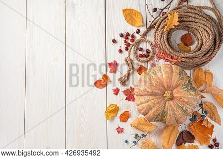 Pumpkin, Autumn Leaves And Berries On A White Wooden Background. Autumn Festive Background. The Conc