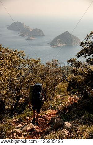 Rear View Of Tourist With Backpack. Hike Along The Lycian Trail