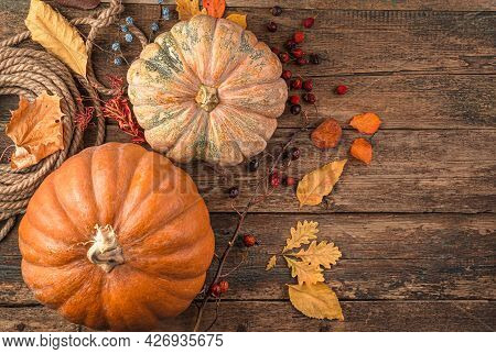 Pumpkin Dry Leaves On A Wooden, Brown Background. Autumn Background. Top View, Copy Space.