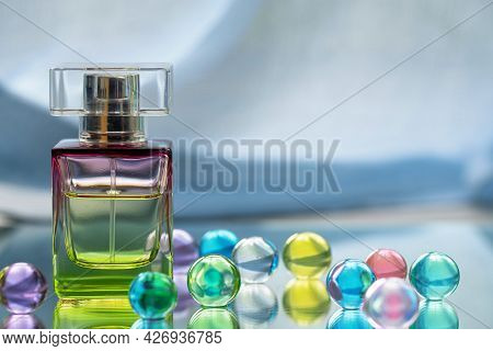 Perfume Bottle With Glass Colored Balls On A Light Background. Perfumes, Cosmetics, A Collection Of
