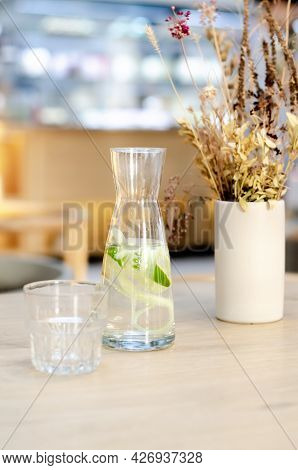 Water With Lemon And Cucumber In A Glass Bottle. Sassy Water For Detox Or Diet On A Wooden Table In