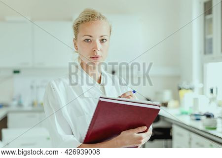 Portrait Of Young, Confident Female Health Care Professional Taking Notes During Inventory In Scient