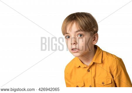 Emotions Of Surprise On The Face Of A Caucasian Boy In A Yellow Shirt. The Child Looks Carefully. Wh