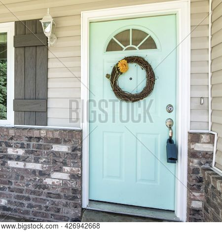 Square Frame Entrance Of A House With Brick Walls And Vinyl Sidings