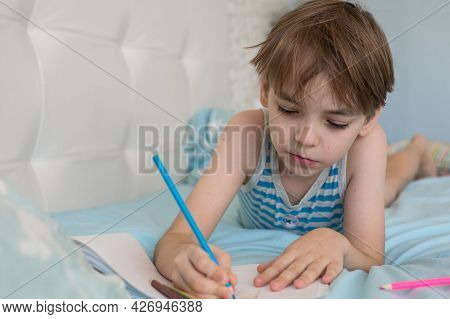 Caucasian Boy Lies On The Bed In The Morning And Draws With Pencils On Paper. The Student Is Passion