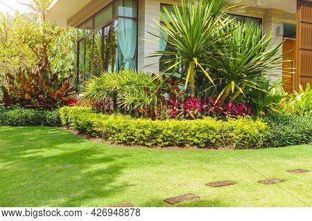 Modern House With Beautiful Landscaped Front Yard, Garden With Fresh Green Grass Both Shrub And Flow