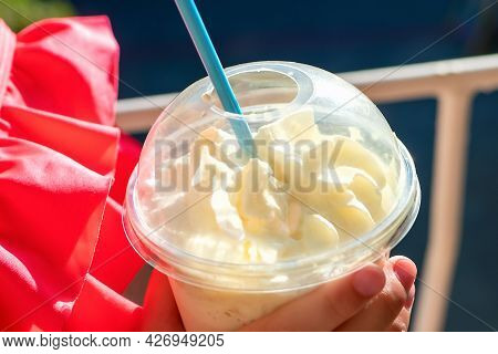 Close Up And Soft Focus Of A Plastic Glass With A Straw With A Milkshake And Whipped Cream In The Ha