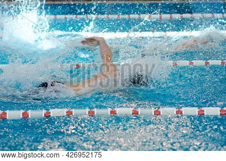 A Beanie Swimmer Stretches Out His Arms During A Breaststroke Workout In The Pool, Blurred Focus