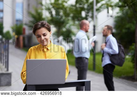 Business And Finance Industry Concept. Attractive Brunette Businesswoman In Yellow Blouse Using A La