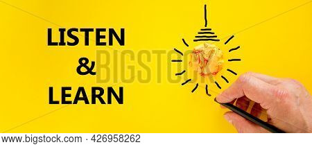 Listen And Learn Symbol. Businessman Writing Words 'listen And Learn', Isolated On Beautiful Yellow