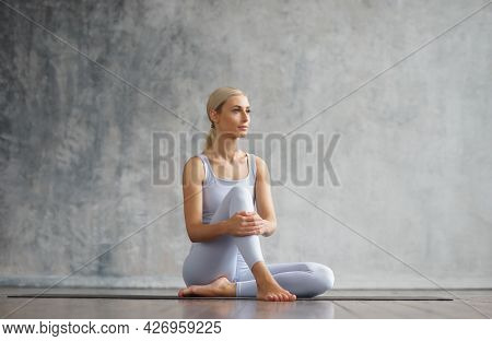 Young And Sporty Girl In Sportswear Is Doing Yoga Exercises In Home Interior. Fit And Slender Blond