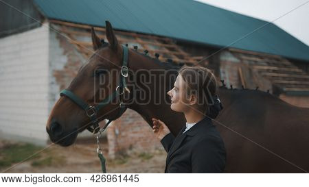 Female Horse Owner Holding The Bridle Of Her Dark Brown Horse Outside The Stable. Smiling At Her Hor