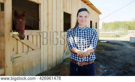 Horsewoman With Horse Feeds In Her Hands Posing For The Camera. Horse Stable With Stalls In The Back
