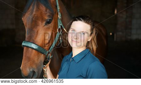 Horse Woman Posing With Her Seal Brown Horse In The Stable Holding The Stallion. Girl Smiling At The