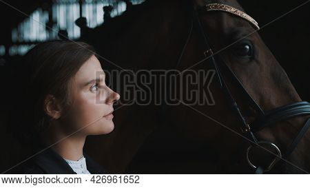 Horsewoman Posing With Her Seal Brown Horse. The Girl Is Dressed In A Black Coat. The Horse Is Weari
