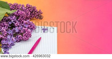 Notepad With Pen And Flowers. Spiral Notebook And Pen. Notebook Lilacs On Yellow Background.