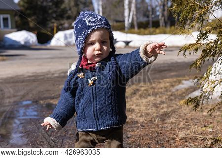 Close Up Shot Of A Cute Canadian Baby Boy With Blue Winter Jersey And Winter Wool Playing Outdoor In