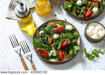 Healthy Diet Salad With Arugula, Mozzarella, Mussels And Vinaigrette Dressing On A Gray Stone Tablet