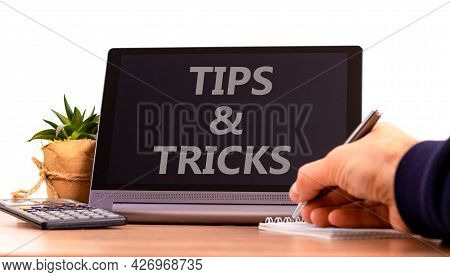 Tips And Tricks Symbol. Tablet With Words 'tips And Tricks'. Businessman Hand With Pen, House Plant.