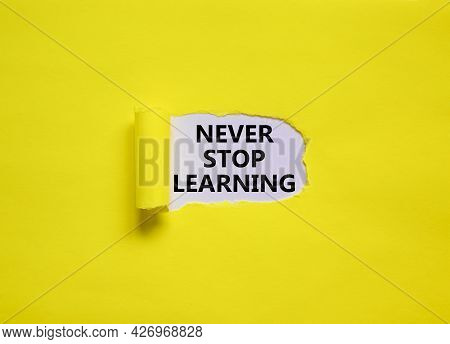 Never Stop Learning Symbol. Words 'never Stop Learning' Appearing Behind Torn Yellow Paper. Beautifu