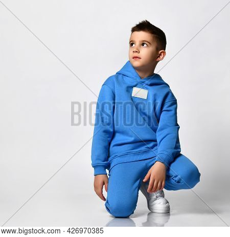Cool Schoolboy In Trendy Bright Blue Sportswear Sits On A White Background. The Child Looks At The E