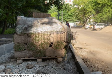 Rolls Of Grass Turf Piled Up On The Sidewalk Of A Moscow Street During Road Repairs